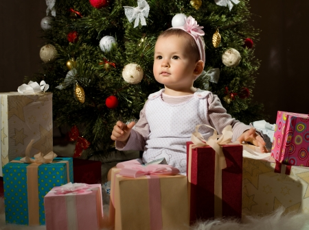 solemnization: one-year-old little girl solemnize Christmas, sit under Christmas-tree with gift