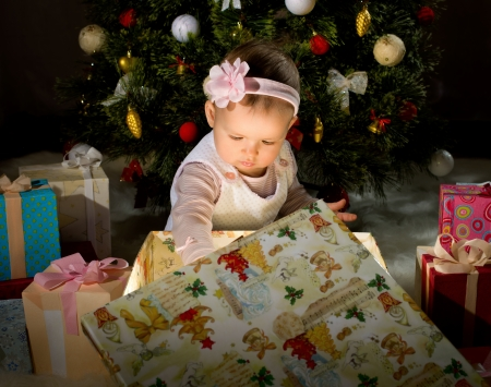 solemnization: one-year-old little girl solemnize Christmas, sit under Christmas-tree and reach gift of box