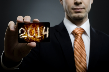 businessman in black costume and orange necktie reach out on camera and show credit card with date 2014 photo