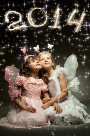 two beautiful little girl with wings, sit and  smile on dark background photo