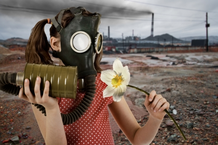 little girl  in gas mask, smell big white flower photo