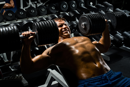 very power athletic guy ,  execute exercise press with  dumbbells, in sport hall Stock Photo - 23378624