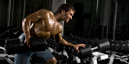 very power athletic guy ,  execute  traction with  dumbbells, exercise on broadest muscle of back, in sport hall Stock Photo - 23378625