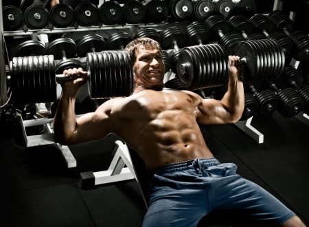 very power athletic guy ,  execute exercise press with  dumbbells, workout  in sport hall Stock Photo - 23758425