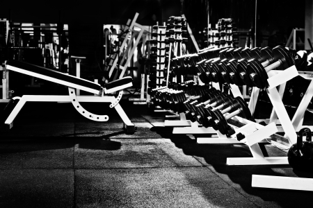 many black dumbbells in dark weight room, horizontal photo
