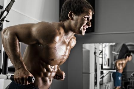 hombre deportista: muy potencia atl�tica chico, ejecutar el ejercicio en las barras paralelas, ejercicio en el pabell�n de deportes Foto de archivo