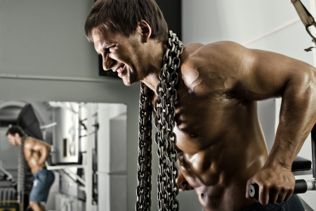 very power athletic guy ,  execute exercise on parallel bars, workout  in sport hall Stock Photo