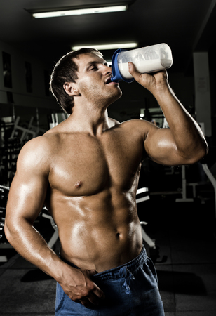 the very muscular sporty  guy drinking  protein in dark weight room, naked  torso photo