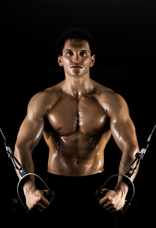 musculation: bodybuilder guy , workout on gym apparatus, on black background