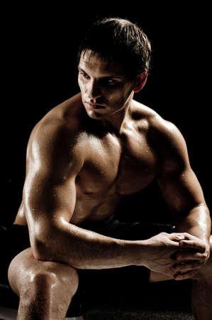 bodybuilder man: very power athletic guy rest  after execute exercise, on black background
