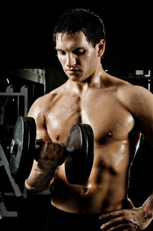 musculation: very power athletic guy ,  execute exercise press with  dumbbells, workout  in sport hall