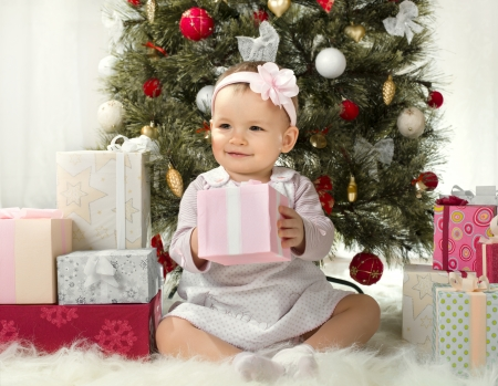 one-year-old little girl solemnize Christmas, sit under Christmas-tree with gift Stock Photo - 23867844