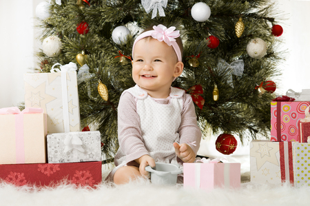 one-year-old little girl solemnize Christmas, sit under Christmas-tree with gift Stock Photo - 23758435