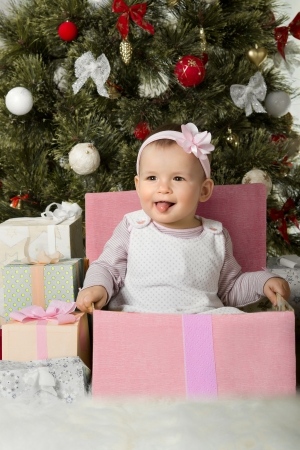 solemnization: one-year-old little girl solemnize Christmas, sit under Christmas-tree with gift, vertical photo