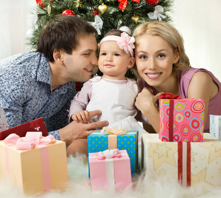 solemnize: portrait very happy family in home with Christmas-tree and gift, smile