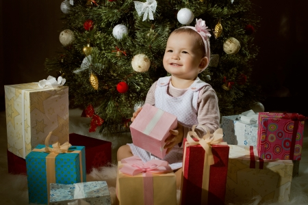 solemnize: one-year-old little girl solemnize Christmas, sit under Christmas-tree with gift