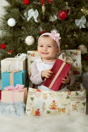 one-year-old little girl solemnize Christmas, sit under Christmas-tree with gift, vertical photo photo