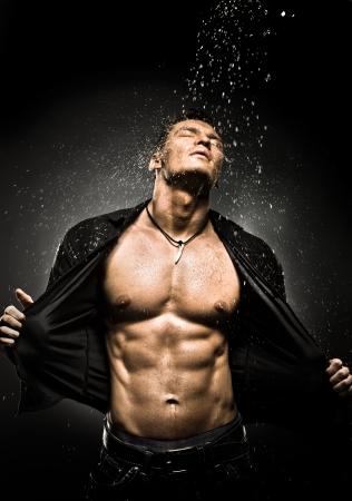 アスリート: シャワーの下で非常に筋肉質のハンサムなセクシーな男