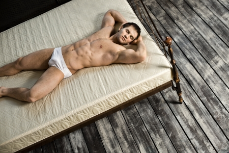 man underwear: the very muscular handsome sexy guy, sleeping  lie on bed,  in  bedroom
