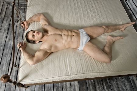 the very muscular handsome sexy guy lie on bed  in  bedroom photo