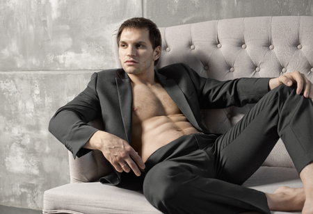 athletic type: the very muscular handsome sexy guy in black  suit indoor Stock Photo