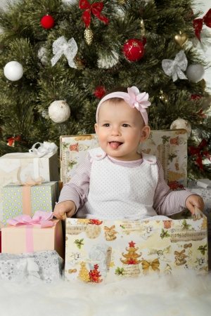 solemnize: one-year-old little girl solemnize Christmas, sit under Christmas-tree with gift, vertical photo