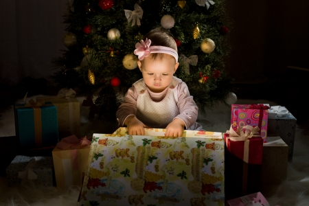 solemnize: one-year-old little girl solemnize Christmas, sit under Christmas-tree and reach gift of box, horizontal photo