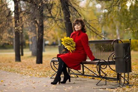 belle: The  mature beautiful woman in red topcoat,  outdoor in park, autumnal day
