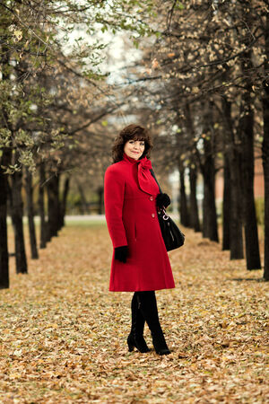 topcoat: The  mature beautiful woman in red topcoat,  outdoor in park, autumnal day