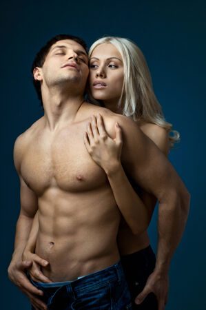 vehement: muscular handsome sexy guy with pretty woman, on dark blue  background, glamour  light
