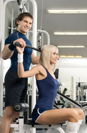 girl and guy,  execute exercise on sport-apparatus , in  sport-hall photo