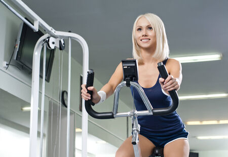 happy cutie athletic girl ,  execute exercise on exercise bicycle  and smile, in  sport-hall photo