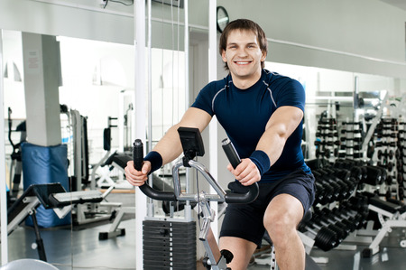 vigorous: young joy  athletic guy,  execute exercise on exercise-bicycle, in  sport-hall Stock Photo
