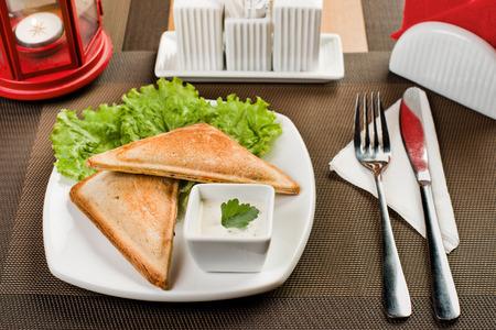 baked  goods: ceramic white plate with baked goods stuffed vegetables, on table in restaurant Stock Photo