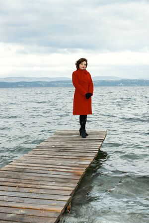 topcoat: beauty mature woman in red topcoat, outdoor on water moorage for boat, in autumn cold overcast day Stock Photo