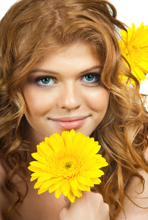 freckled: the very  pretty red-haired blue eyed young woman  with yellow flower,  smile ,vertical close up portrait