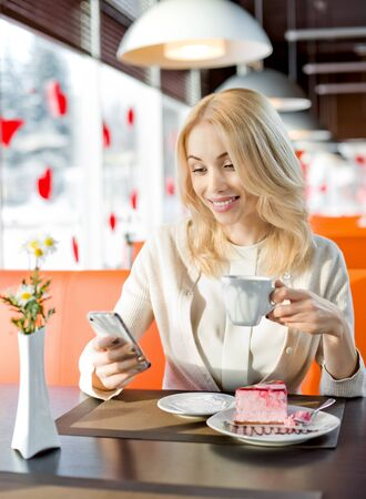 inet: Very beautiful, happy,  young woman, sit in  Cafe with telephone, vertical portrait