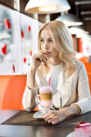 pensiveness: Molto bella giovane donna triste, si siede in caff� e bere caff�-cocktail, ritratto verticale