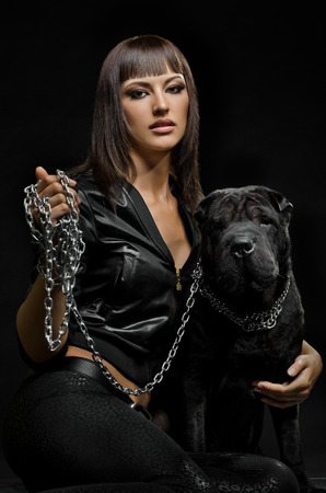 aegis: the beautiful  young woman sit with dog on black background