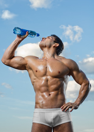 quench: the very muscular handsome sexy guy on sky background, drink water, focus on face