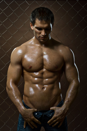 gaol: the very muscular handsome sexy guy ,  on  netting   steel fence Stock Photo