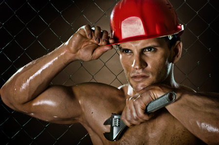 miry: closeup portrait  the beauty muscular workman, in red safety helmet  with big   adjustable wrench  in hand, sordid and sweaty