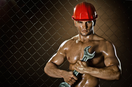 body builder:  the beauty muscular worker  man, in  safety helmet  with big wrench  in hands, on netting fence background Stock Photo