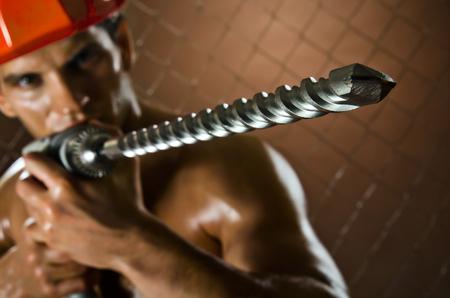 man close up: la bellezza lavoratore trapano uomo vicino, maneggiare con perforatore