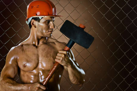 muscular worker , in  safety helmet  with big tup  in hands, on netting fence background photo