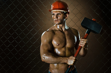 enginery: muscular worker , in  safety helmet  with big tup  in hands, on netting fence background