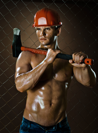 ax man: the beauty muscular worker  chopper  man, in  safety helmet  with big  heavy ax  in hands,  on netting fence background