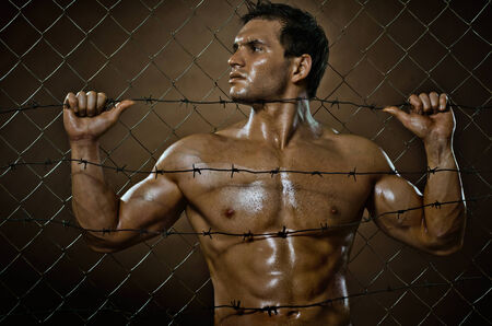 the very muscular handsome felon guy ,  out of netting   steel fence photo