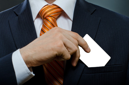 take out: businessman in black costume and orange necktie put or take out credit card in pocket Stock Photo
