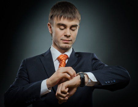 young businessman in black costume wind clock (wristwatch) on hand, closeup photo
